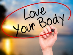 Man Hand writing Love Your Body with black marker on visual screen. Business, technology, internet concept.